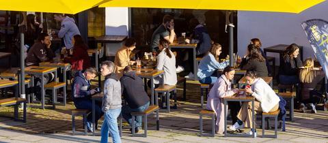 Menschen sitzen unter einer Markise im Außenbereich eines Cafés.