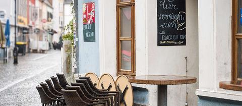 """Foto von gestapelten Stühlen und Tischen, wie sie vor einer Gaststätte stehen. An der Wand hängt eine Tafel auf der steht: """"Wir vermissen euch."""""""