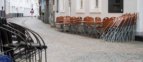 Foto von einer leeren Fußgängerzone, die von unbesetzten und gestapelten Gastronomiestühlen und -tischen gesäumt wird.
