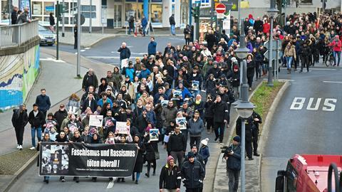 """Eine Demonstration bewegt sich begleitet von wenigen Polizisten die Straße herab. Das Fronttransparent hat die Parole; """"Faschismus und Rassismus töten überall"""""""