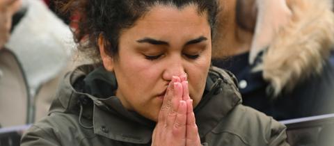 Newroz Duman, ein junge Frau mitte 20, mit sehr lockigen Haare, hat die Hände vor dem Mund wie zum Gebet gefaltet. Sie hält eine Schweigemiunte für die Ermordeten von Hanau ab.