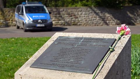 Eine Nelke liegt auf einem Gedenkstein, auf dem Namen eingraviert sind. Im Hintergrund steht ein Polizei-Streifenwagen.