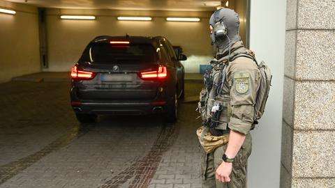 Ein SEK-Beamter sichert die Einfahrt eines Zivilfahrzeugs in das Oberlandesgericht in Frankfurt.