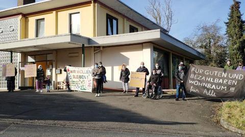 """Foto einer Unterkunft für geflüchtete Menschen in Witzenhausen. Vor dem Gebäude stehen Menschen mit Schildern auf denen unter anderem steht: """"Für guten und bezahlbaren Wohnraum! Für alle!"""" oder """"Wie wollen bleiben"""""""