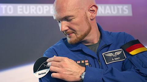 """Der Astronaut Alexander Gerst heftet sich das Logo seiner neuen Weltraummission """"Horizons"""" an den Arm."""