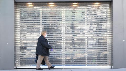 Eine Frau mit Atemmaske läuft vor einem geschlossenen Geschäft in Frankfurt vorbei.