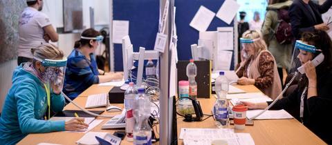 Mitarbeiterinnen eines Gesundheitsamts am Telefon, um Infektionsketten in der Corona-Pandemie nachzuspüren, geschützt durch Trennwände und Gesichtsvisier