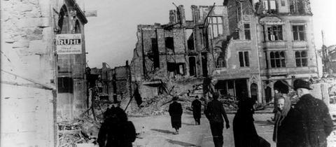 Menschen gehen über den zerstörten Gießener Marktplatz 1944