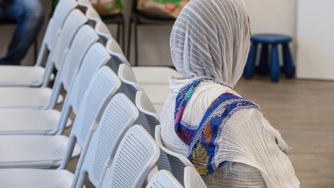 Eine Frau mit Kopftuch wartet im Ankunftszentrum in Gießen