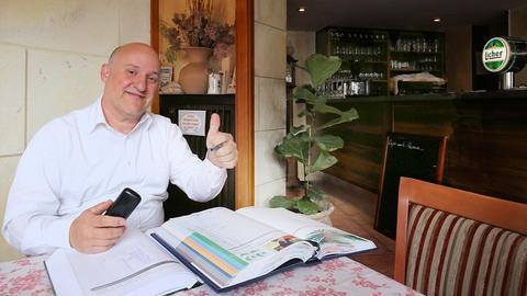 Giovanni Infurna in seinem Lokal La Locanda an einem Tisch sitzend, das Buchungsbuch und ein Telefon vor sich und seinen Daumen nach oben hebend.
