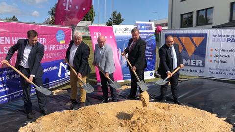 Fünf Männer mit Schaufeln vor einem Erdhaufen auf einer Baustelle