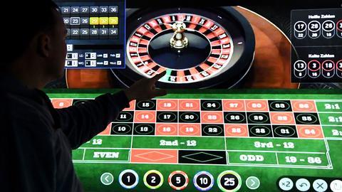Ein Mann steht vor einem Bildschirm mit einer Seite für Online-Roulette