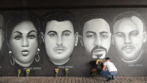 Ein Mann legt Blumen vor dem Graffito der Ermordeten nieder