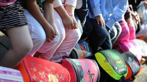 Kinder sitzen mit ihren Schulranzen in einer Reihe