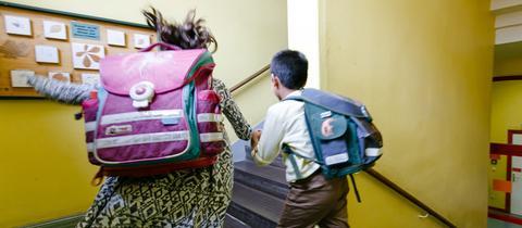 Zwei Schulkinder, die im Treppenhaus die Treppe hochrennen.
