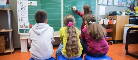Drei Kinder sitzen mit einer Lehrerin von einer Tafel