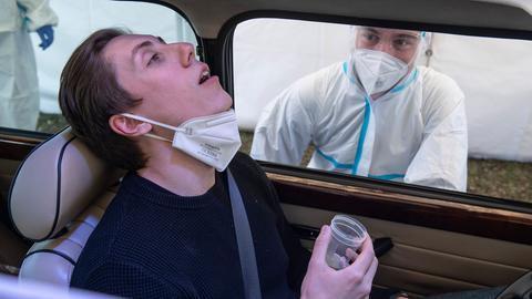 Ein Autofahrer hält einen Becher mit der zu gurgelnden Lösung in der Hand.