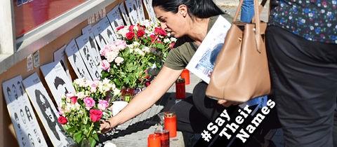 Eine Frau zündet ein Grablich an. Vor einer Mauer sind die Portraitfotos der Opfer des Anschlags vom 19. Februar aufgestellt.