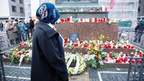 Eine Frau steht im Vordergrund vor den vielen Trauerbekundungen in Form von Blumen, Kränzen und Kerzen an einem Denkmal in Hanau. Im Hintergund sind weitere Menschen zu sehen.