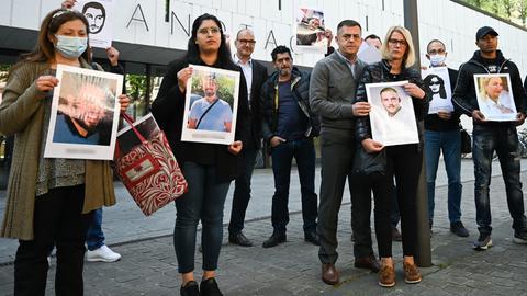 Angehörige er Opfer von Hanau stehen mit Fotos der Toten vor dem Landtag