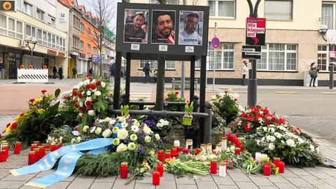 Viele Blumenkränze und Kerzen stehen an dem provisorisch eingerichteten Gedenkort für Opfer des Anschlags in Hanau. In der Mitte des Arrangements Bilder von Gökhan Gültekin, Sedat Gürbüz und Fatih Saraçoğlu