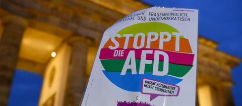 Teilnehmer gedenken der in Hanau getöteten Menschen bei einer Mahnwache am Brandenburger Tor und halten ein Anti-AfD-Schild hoch.