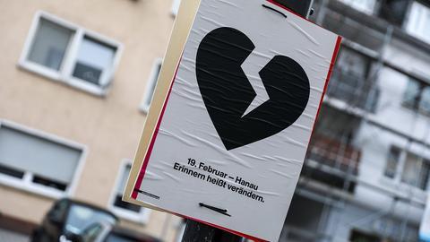 Auf einem Plakat ist ein gebrochenes schwarzes Herz abgebildet.