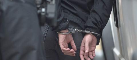Ein mit Handschellen gefesselter Mann und ein Polizist.