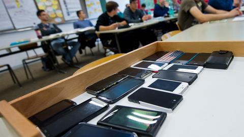 Eingesammelte Handys liegen in einer Schulklasse.