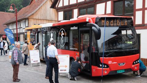 Ein sogenannter Medibus, eine Arztpraxis auf Rädern, steht in einem hessischen Dorf. Menschen begutachten das Fahrzeug.