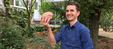 Und da sollen Gedanken rauskommen? Henning Beck zeigt ein menschliches Gehirn.