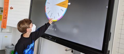 Ein Schüler der Herderschule bedient die digitale Tafel.