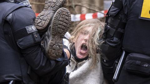 Polizisten tragen Demonstranten aus dem Herrenwald bei Stadtallendorf.