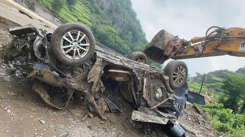 Ein Bagger zieht ein völlig zerstörtes Auto von einer schlammgefluteten Straße.