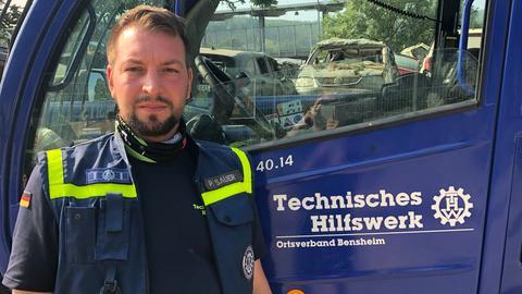 THW-Helfer Philipp Sauer vor einem Einsatzfahrzeug.