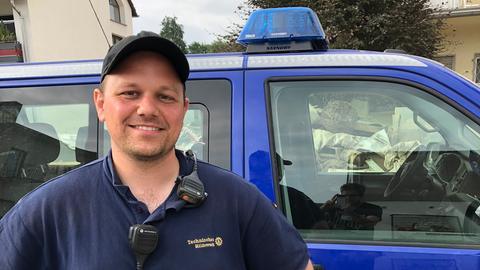 THW-Helfer David Wellenreuther vor einem THW-Fahrzeug