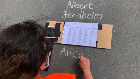 """Eine Teilnehmerin der Aktion """"Schreiben gegen das Vergessen"""" schreibt den Namen eines Frankfurter Opfers des Holocausts auf die Straße"""