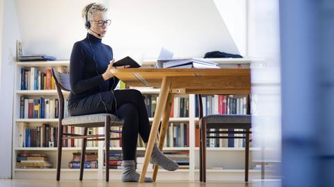 Eine  Frau sitzt am Wohnzimmertisch mit einem Laptop vor sich und einem Headset auf dem Kopf. Sie telefoniert und schaut in ihren Kalender.