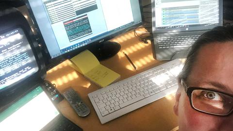 Selfie - Caroline Wornath an ihrem Schreibtisch mit zwei Laptops, Monitor und TV.