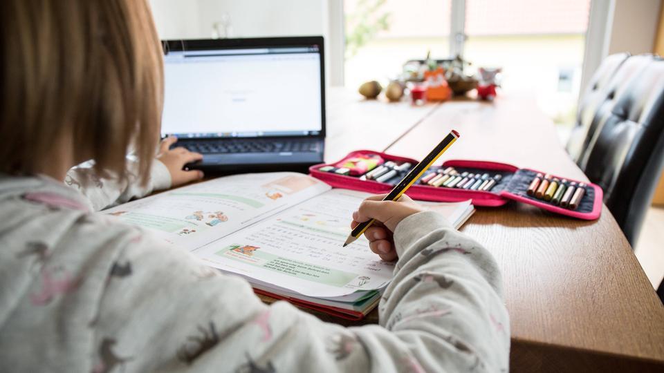 Ein Grundschulkind sitzt mit einem Buch vor dem Laptop