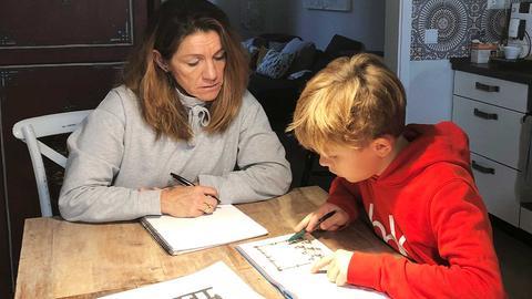 Der Schüler Teo sitzt mit seiner Mutter am Küchentisch und gemeinsam arbeiten sie an seinen Aufgaben.