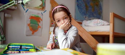 Ein Mädchen sitzt lustlos vor ihren Hausaufgaben