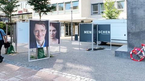 """Im Außenraum, an der Treppenstraße in Kassel sind Bilder und Texte auf und ausgestellt. Im Vordergund ist zum Beispiel ein großes Portrait von Kai Lauterbach zu sehen. Auf einer Tafel daneben steht der Text """"Menschen""""."""