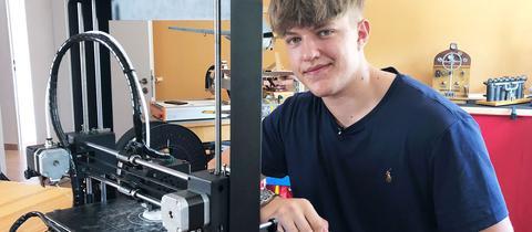 Portrait von Felix Kläres. Er sitze neben seinem 3D-Drucker, im Hintergrund ist seine Werkstatt mit technischen Geräten zu sehen.