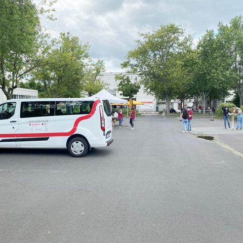 """Auf einem Parkplatz der Uni Gießen steht ein Kleinbus mit der Aufschrift """"Impfzentrum"""". Drumherum sind Stehtische zu sehen, an denen junge Menschen stehen."""