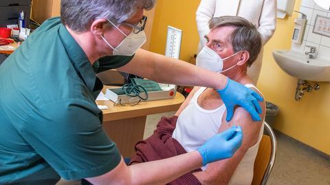 Foto, wie ein Hausarzt einem Patienten eine Impfdosis in seiner Praxis verabreicht.