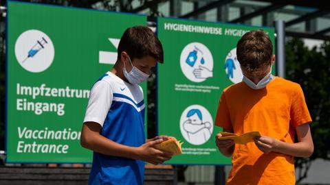 Zwei Jungen stehen vor einem Impfzentrum