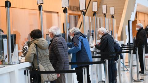 Impfpatienten stehen im Wiesbadener Impfzentrum im Kongresszentrum RMCC an den Registrierungsschaltern.