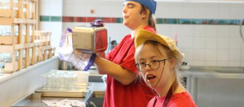 Zwei Frauen mit Behinderung arbeiten in der Küche