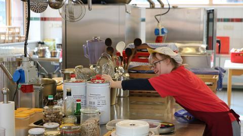 Eine Frau mit Behinderung greift nach einem Küchengerät auf einem Tisch.